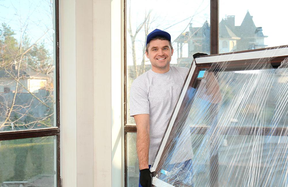 Lächelnder Glaser trägt Fensterscheibe